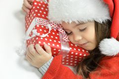 Girl  sleeping  with Christmas present. Portrait of happy girl in Santa hat sleeping  with Christmas present Royalty Free Stock Photos