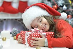 Girl sleeping with Christmas present. Portrait of happy girl in Santa hat sleeping with Christmas present stock image