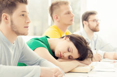 Girl sleeping in the classroom during the lessson. Student sleeping on a lesson. Tired and depressed girl Stock Image