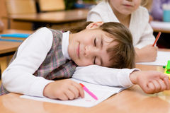 Girl sleeping in classroom Stock Photo