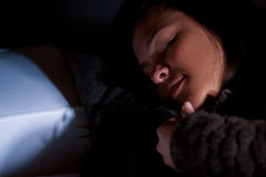 Girl sleeping on a couch in half-light Stock Image