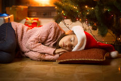 Girl sleeping on floor at fireplace under Christmas tree Royalty Free Stock Photography