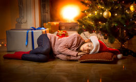 Girl sleeping on floor under Christmas tree next to fireplace Stock Photos