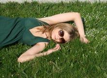 Girl sleeping among flowers. On grass Royalty Free Stock Photo