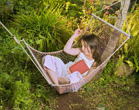 Girl sleeping in a hammock. Little girl sleeping in a hammock with a book Royalty Free Stock Photos