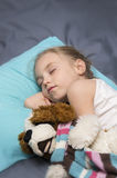 Girl sleeping with her a favorite toy Stock Image
