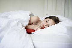 Girl Sleeping With Hot Water Bottle In Bed Royalty Free Stock Photography