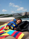 Girl sleeping in life jacket. Young girl sleeping in life jacket under blanket on boat Royalty Free Stock Images