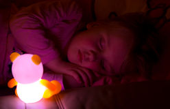 Girl sleeping with light toy. A night photo of a little girl sleeping with a lit light toy Stock Image