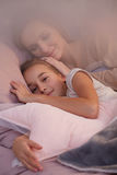 Girl sleeping with mother Stock Images