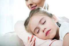 Girl sleeping on mother`s arm at home Stock Photo