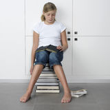 Girl sleeping over her books stock image
