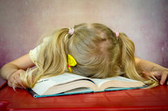Girl sleeping over open book Stock Photo