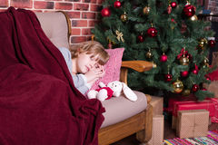 Girl sleeping on sofa near Christmas tree with gifts Stock Photo
