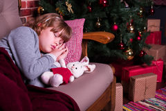 Girl sleeping on sofa near Christmas tree with gifts Royalty Free Stock Photo