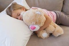 Girl sleeping on sofa with stuffed toy Royalty Free Stock Image