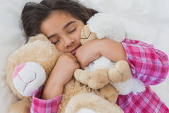 Girl sleeping with stuffed toys in bed Stock Images