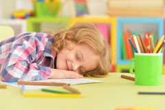 Girl sleeping on table. Portrait of a cute little girl sleeping on table Royalty Free Stock Photography