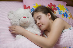 Girl sleeping with teddy bear. A young girl sleeping holding a teddy bear Royalty Free Stock Image