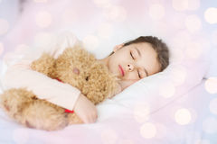 Girl sleeping with teddy bear toy in bed at home Stock Photos