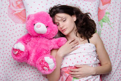 Girl sleeping with teddy bear Stock Images