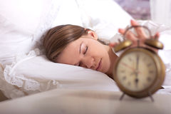 Girl is sleeping and turns off the alarm Royalty Free Stock Photos
