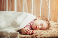 Girl sleeping under a blanket. daytime sleep child. The benefit of sleep in the middle of the day stock photography