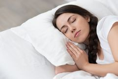 Girl sleeping on white bed royalty free stock image