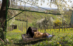 Girl Sleeping on a wineyard. A young woman sleeps on a swing in a wineyard under a cherry tree Royalty Free Stock Photography