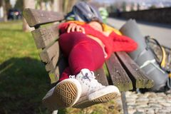 Girl sleeping on wood bench outdoors. Outside female lying Stock Photography
