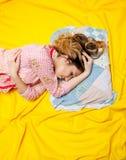 Girl sleeping on the yellow sheet Stock Photography