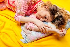Girl sleeping on the yellow sheet Stock Image