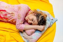 Girl sleeping on the yellow sheet Royalty Free Stock Photos