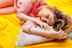 Girl sleeping on the yellow sheet Stock Photos