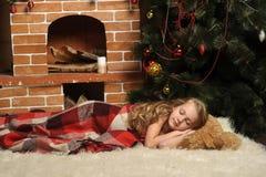 Girl sleeps beside a Christmas tree Royalty Free Stock Image