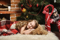Girl sleeps beside a Christmas tree Stock Photos