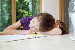 Girl sleeps on homework Royalty Free Stock Photo