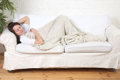 Girl sleeps on a soft divan. Young girl sleeps on a soft divan Royalty Free Stock Photos