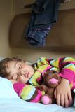 Girl sleeps in train with puppet. Little girl sleeps in train with puppet Stock Photography