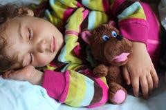 Girl sleeps in train with puppet. Little girl sleeps in train with puppet Royalty Free Stock Photo