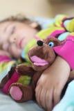 Girl sleeps in train with puppet. Little girl sleeps in train with puppet Royalty Free Stock Photography