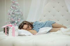 Girl sleeps in a white round bed near a pillow stands a christmas present in the bedroom with a new year tree Royalty Free Stock Images