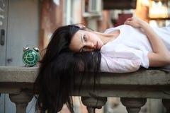 Girl sleepyhead. Sleepyhead girl sleeping on the street on the banisters Stock Photo