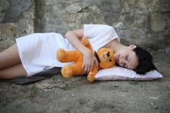 Girl sleepyhead. Sleepyhead girl sleeping on the street with teddybear Stock Image