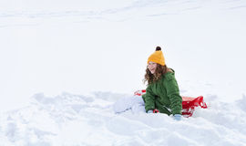 Girl with sleigh sitting in snow. Smiling teenager girl with red plastic sledge sitting in snow Stock Photo