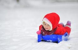 girl on sleigh in winter time Stock Photos