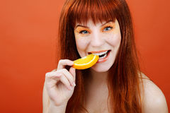 Girl with slice of orange Royalty Free Stock Images