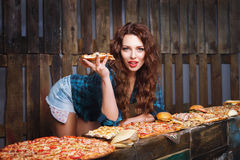 Girl with slice of pizza promotes fast food. Fastfood advertise Stock Photo