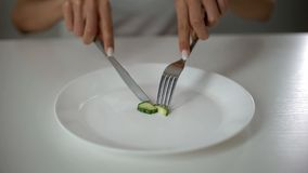 Girl slicing cucumber, obsessed with undereating, fear of overweight, anorexia. Stock photo stock photography