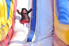 A girl on a slide. A smiling girl enjoying an inflated bouncy slide Royalty Free Stock Image